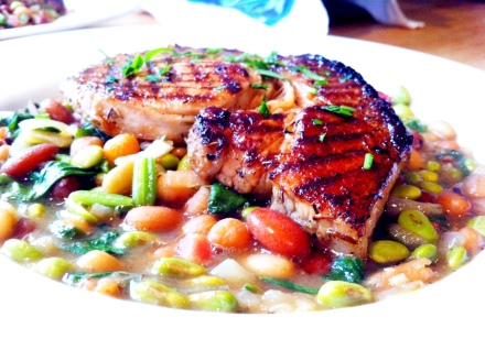 My summery take on a classic pork and beans recipe. Grilled lemon & thyme pork chops with a bean stew cooked with cider.
